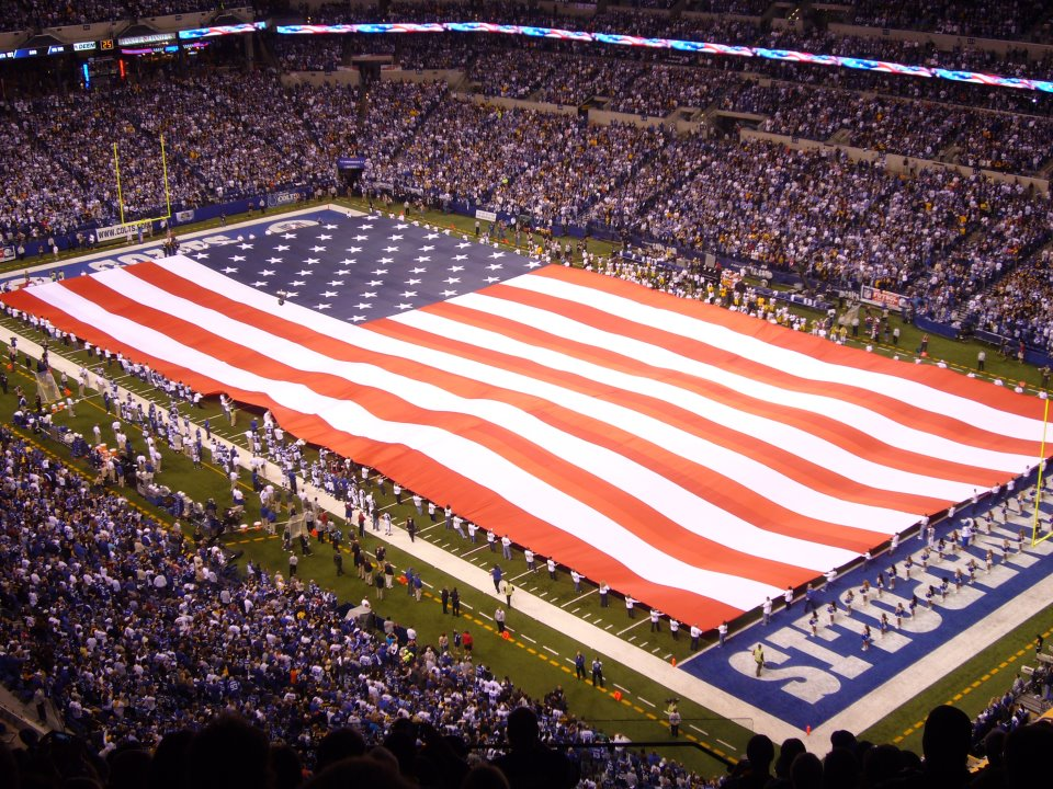 Image of an American flag covering the entire length of a football field.