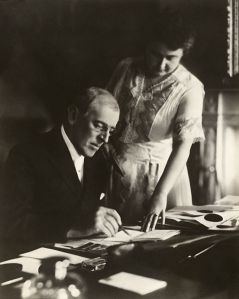 President Woodrow Wilson, seated at desk with his wife, Edith Bolling Galt, standing at his side. First posed picture after Mr. Wilson's stroke partially paralyzed his left side, White House, June 1920. Mrs. Wilson holds a document steady while the President adds his signature.