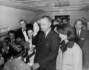 Lyndon B. Johnson taking the oath of office on Air Force One two hours and eight minutes after the assassination of John F. Kennedy. Judge Sarah T. Hughes became the first woman to swear in a new President.