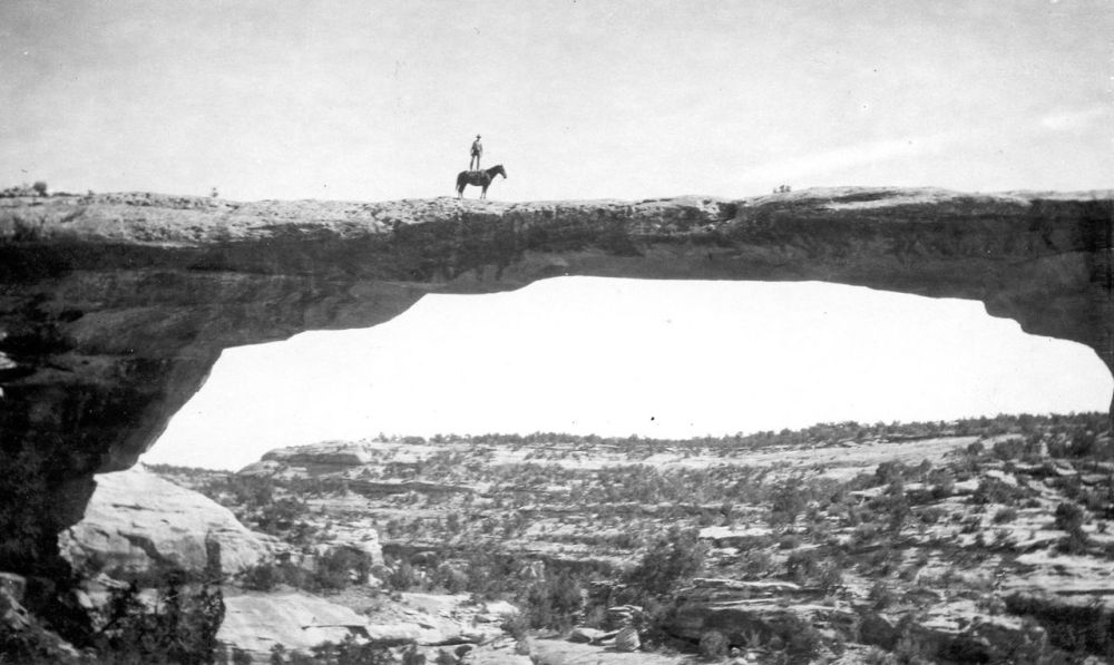 "Natural Bridges National Monument in Utah. Dan Perkins (USGS employee) standing on his horse ""Cap"" on top of Owachomo Bridge. Circa 1925. Photo: WT Lee, USGS. Posted by the US Department of the Interior on Tumblr, 4/24/14."