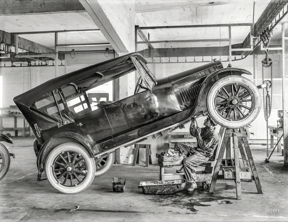 "Circa 1919. ""Studebaker motor car in repair shop with garage mechanic."" Don't try this at home. Or at work. 6.5 x 8.5 inch glass negative from the Wyland Stanley collection of San Francisco historical memorabilia."
