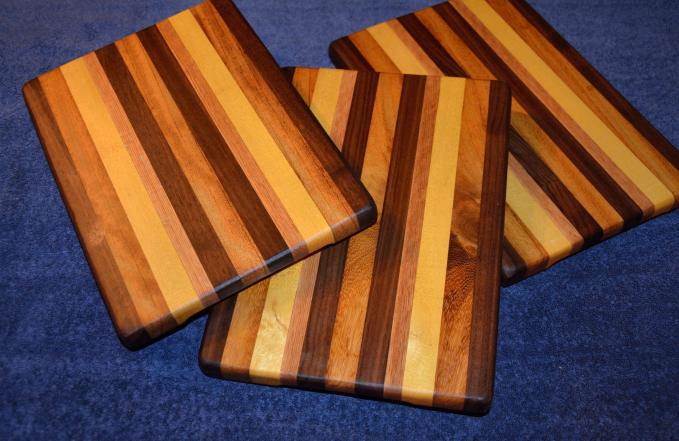 "# 17 Cheese Board, $35. Edge grain. Walnut, teak, and yellowheart. 11"" x 8"" x 1""."