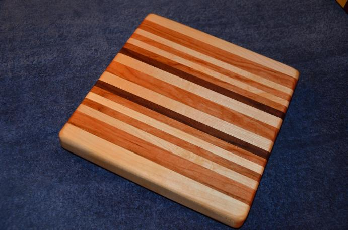 "# 23 Cutting Board, $50. Edge grain. 12"" x 12"" x 1-1/2"". Maple, cherry and walnut."