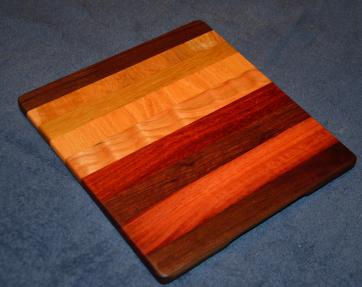 "Cheese Board # 15 - 006. Black Walnut, Cherry, Padauk, Jarrah, Curly Cherry, Honey Locust, Teak and Birdseye Maple. 12"" x 11"" x 5/8""."