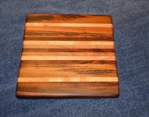 "Cheese Board # 13 - 00. This is the board that started it all ... the first cheese board I ever made, and gave to Velda for Christmas. Board has been resurfaced after 2 years of use, and the rubber feet have been replaced with the upgraded version I started using immediately after making the board. Goncalo Alves, Honey Locust, Jatoba, Black Walnut and Cherry edge grain. 10"" x 11"" x 1""."