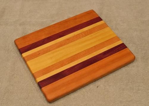 "Cheese Board # 15 - 057. Cherry, Purpleheart, Hard Maple & Yellowheart. 9"" x 11"" x 3/4""."