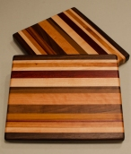 "Cheese Board 16 - 001. Chaos boards. Black Walnut, Hard Maple, Canarywood, Purpleheart, Padauk & Cherry. Edge grain. 10"" x 11"" x 1""."
