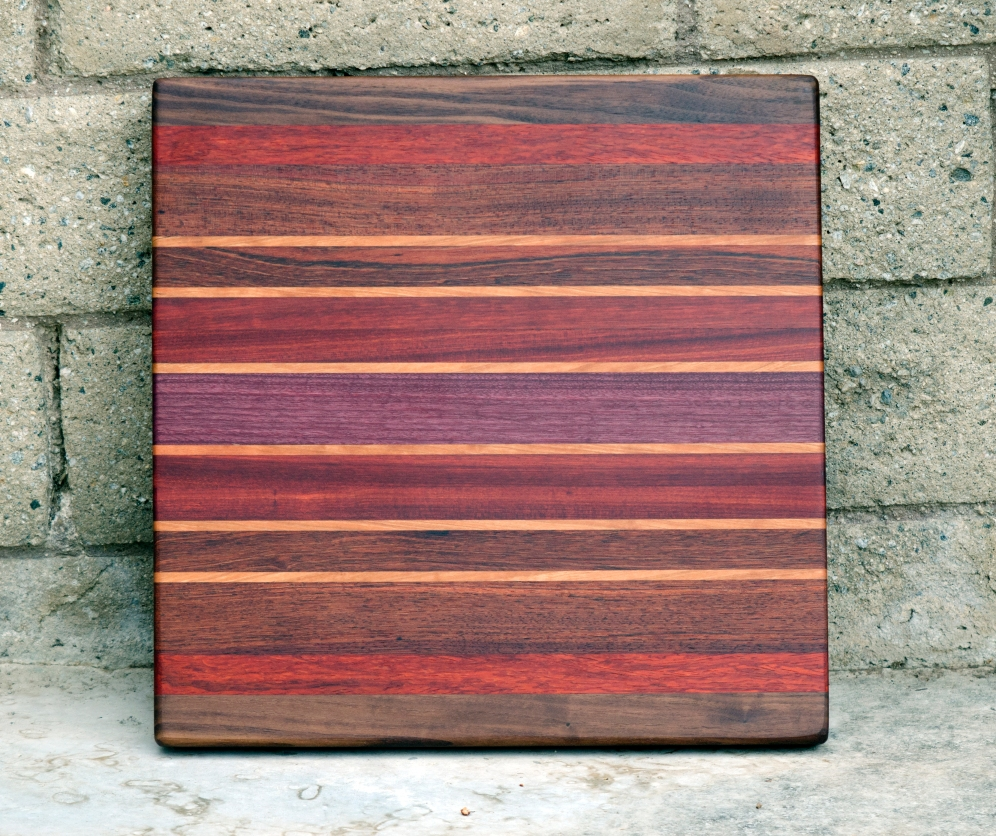 "Cutting Board 16 - Edge 002. Purpleheart, Black Walnut, Bloodwood, Padauk, Cherry & Jatoba. 16"" x 16"" x 1-3/8""."
