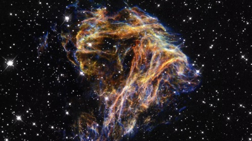 DEM L 190 Resembling the puffs of smoke and sparks from a summer fireworks display, these delicate filaments are actually sheets of debris from a stellar explosion in a neighboring galaxy. Denoted N 49, or DEM L 190, this is the remnant of a massive star that died in a supernova blast whose light would have reached Earth thousands of years ago. Photo by the Hubble Telescope.