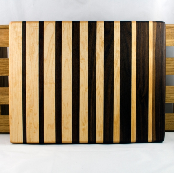 "Cutting Board 16 - Edge 018. Black Walnut & Hard Maple. 12"" x 16"" x 1-1/2"". This board was one of 2 that I made as a set that I was going to cut apart & do something unusual with ... until I discovered that this board had a piece with a void in it. That piece had to be replaced, which means my original plan never got done. The matching board was sold long ago; now this one finally makes it to the finish line."