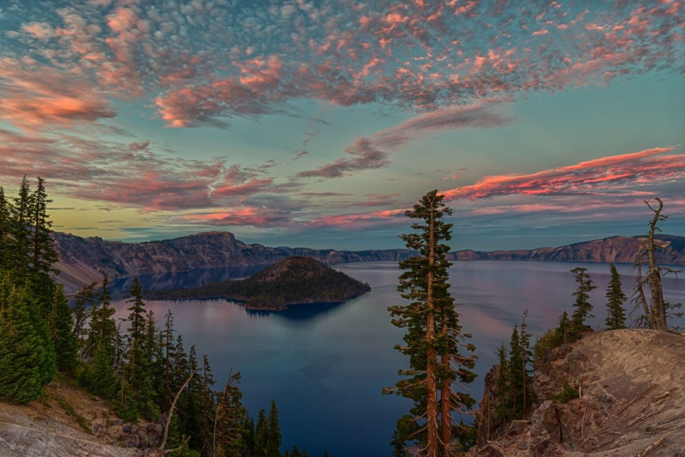 "With pinkish clouds over serene blue waters and stately trees, there's beauty everywhere you look at Crater Lake National Park in Oregon! Photographer Jeff C. Bryant waited until just the right moment to capture this striking sunset shot: ""As someone who photographs sunsets quite often, you win some and lose some. One thing I've learned is not to leave early!"" Photo by Jeff C. Bryant, Posted on Tumblr by the US Department of the Interior, 9/10/16."