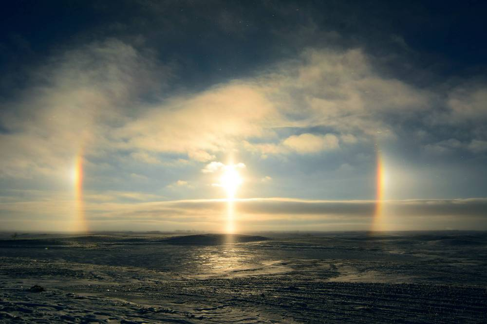 A sun dog (meteorological name: parhelion), also known as a mock sun, or phantom sun, is an atmospheric phenomenon that typically consists of a bright spot to the left and/or right of the sun. Sun dogs are a member of a large family of atmospheric halos, created by light interacting with ice crystals in the atmosphere. Photo by: Rick Bohn/USFWS. Posted on Flickr by the US Fish & Wildlife Service, 1/3/17.