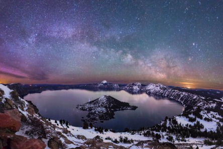 """An unforgettable night sky – with a tinge of color from the Northern Lights – stretches over Crater Lake National Park in Oregon. America's national parks hold some of the last remaining harbors of darkness where visitors can enjoy the splendor of these protected dark skies. Photographer Matthew Newman says his nighttime adventure forever changed the way he experiences nature: """"Making a seven-mile snowshoe hike round trip in the middle of the night to try and capture the Aurora Borealis and Milky Way from this location was amazing."""" Photo by Matthew Newman. Posted on Tumblr by the US Department of the Interior, 1/15/17."""