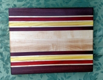 """Engraved 17 - 025. Edge grain cutting board with the back engraved. Purpleheart, Hard Maple, Padauk, Yellowheart & Bubinga. 14"""" x 18"""" x 1-1/4"""". Purchased before it was completed."""